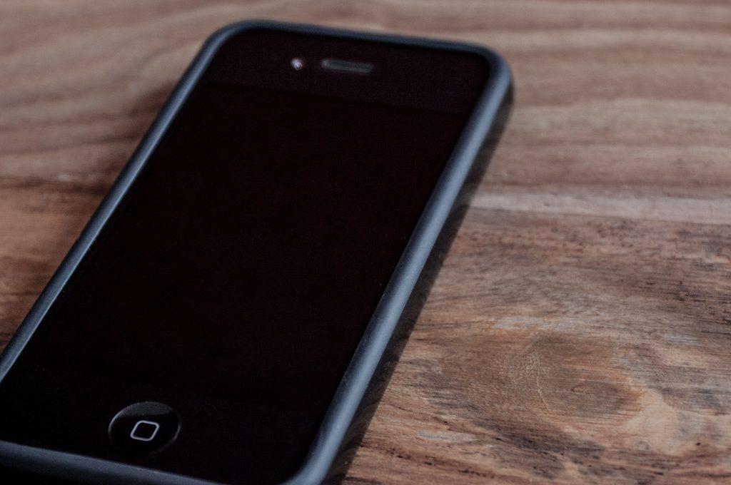 iPhone mit Schutzhülle auf Holztisch