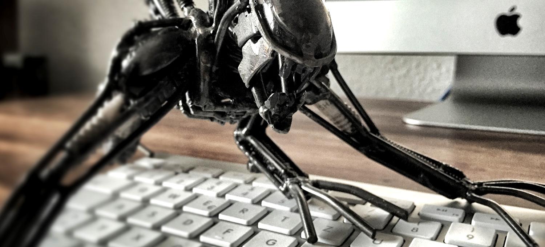 Alien aus Schrott, das auf einer Apple-Tatstatur steht und im Hintergrund ein iMac mit Apple-Logo